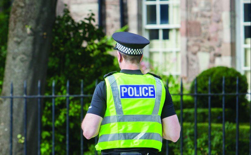 EDINBURGH, SCOTLAND - JULY 21: Police officer on guard duty near the Royal palace. EDINBURGH, SCOTLAND - JULY 21